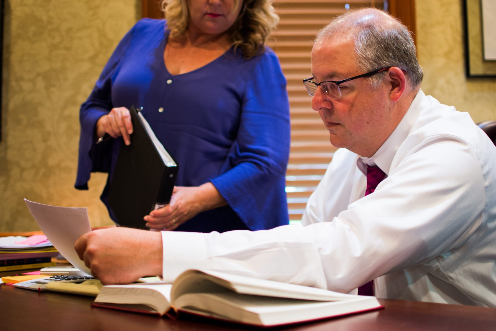 Charles J. Sticklen Jr. reading paperwork at Sticklen & Dreyer Law Firm