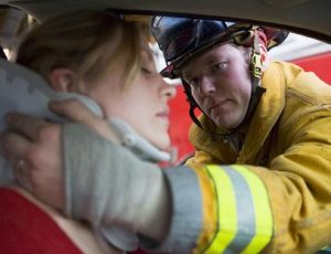 Firefighter putting neck brace on injured woman in car accident.