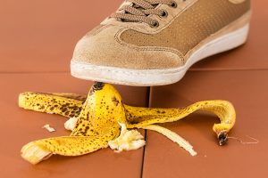 Shoe stepping on a banana peel. Possible slip & fall workers' compensation claim.