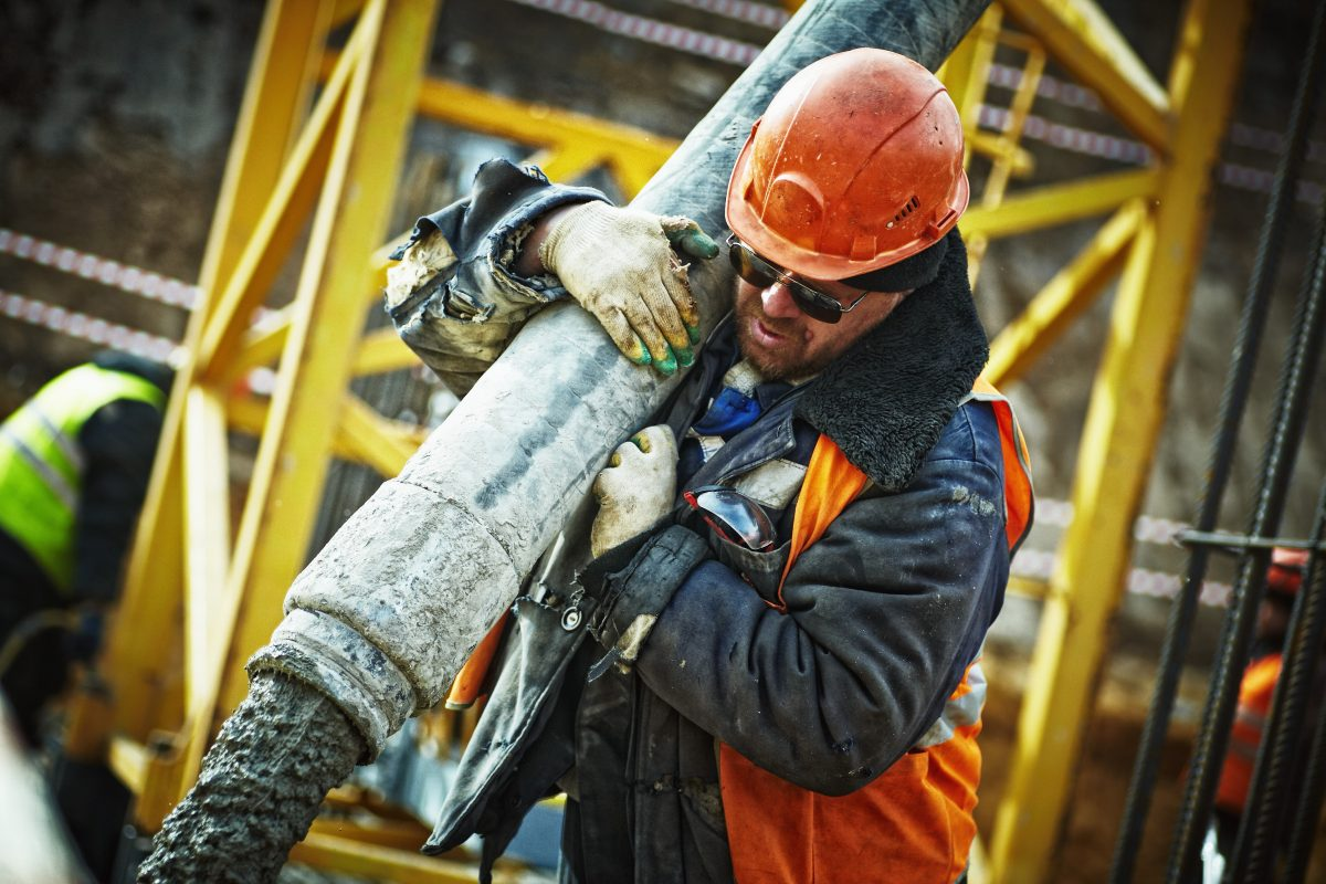 Construction worker carrying large pipe   Workers' Compensation