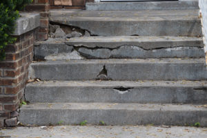 Short set of cement steps is cracked and broken and in need of repair