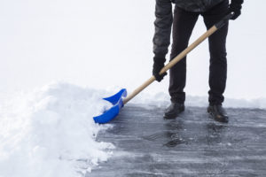 Man cleaning snow with blue shovel from ice surface for ice skating.